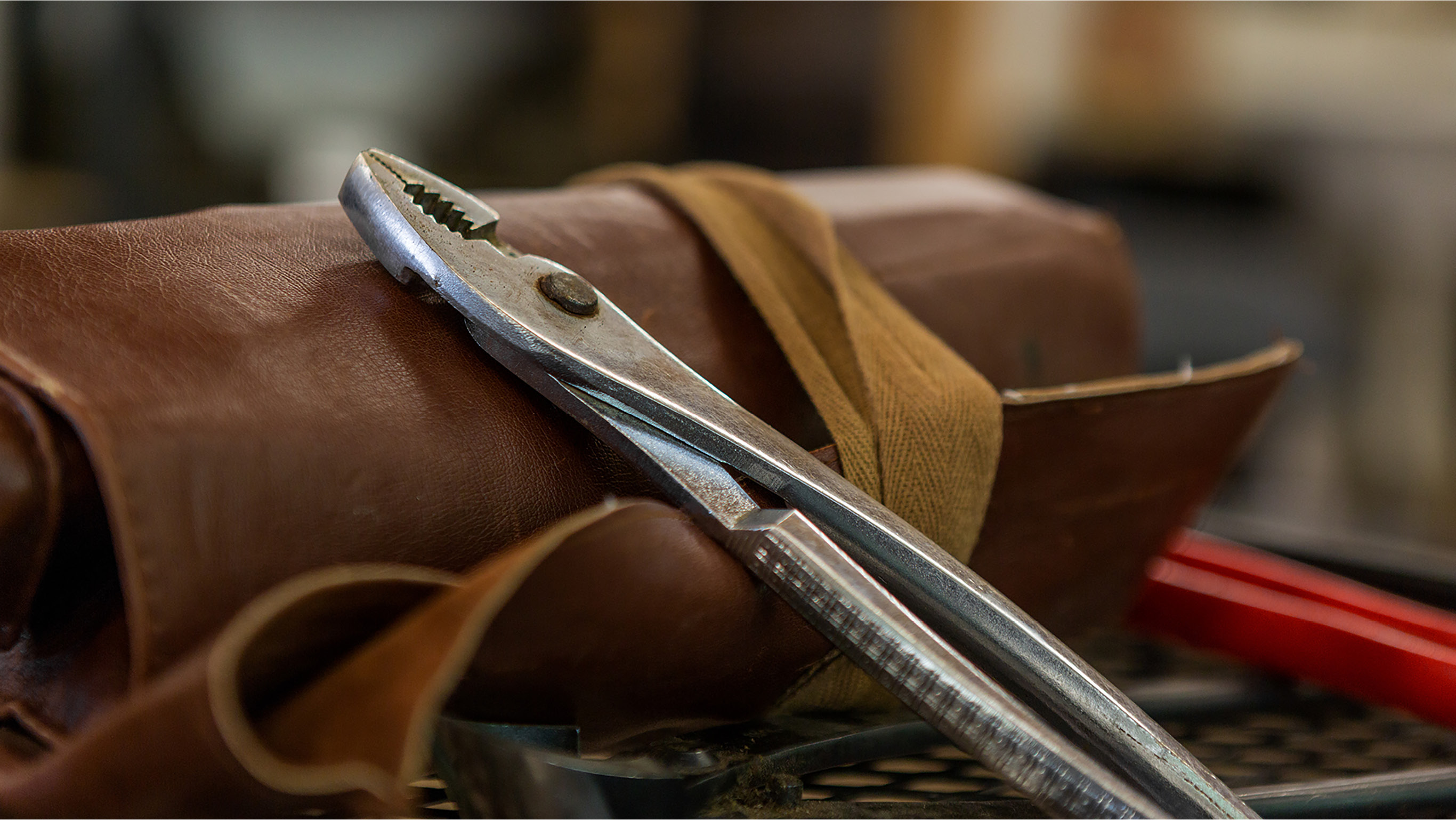 A photo of pliers on top of a leather bonsai tool bag.
